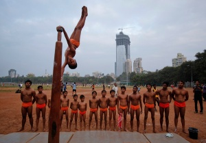 A boy performs a Mallakhamb pose on a pole as others watch.