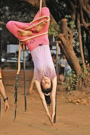 a girl practicing on a rope mallakhamb
