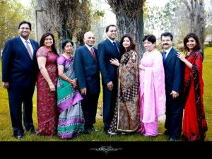 indian family photo where men wear suits and women sarees