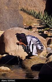 man drinking water by squatting