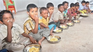 children eating food sitting on floor